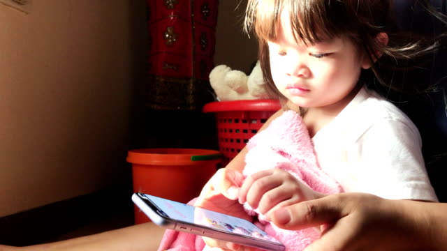 Mother and daughter using smartphone at home video
