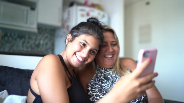 mutter und tochter mit smartphone, während sie auf dem sofa sitzen - brasilianischer abstammung stock-videos und b-roll-filmmaterial