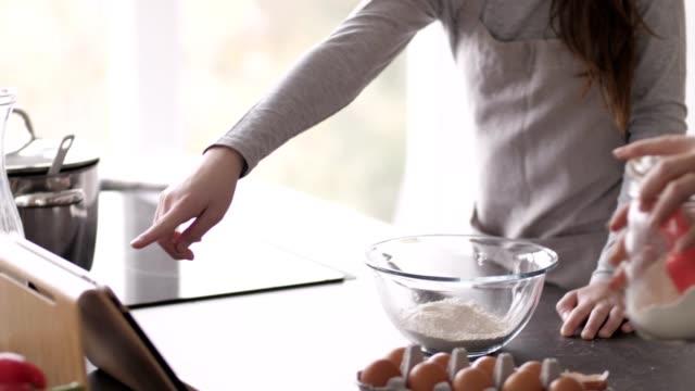 vidéos et rushes de mère et fille utilisant la tablette pendant la cuisson des biscuits - recette