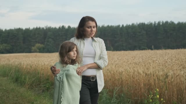 Mother and daughter walking and talking embracing, summer nature field of wheat background Mother and daughter walking and talking embracing, summer nature field of wheat background styles stock videos & royalty-free footage