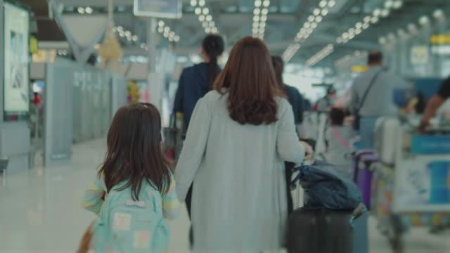 vidéos et rushes de mère et fille marchant à l'aéroport. - adieux