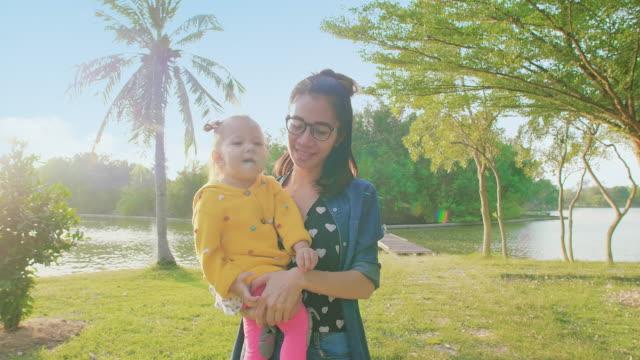 slo mo mother and daughter walking in park - staw woda stojąca filmów i materiałów b-roll
