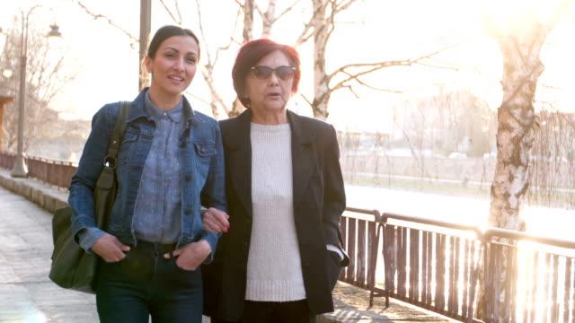 Madre e hija caminando cerca de río - vídeo