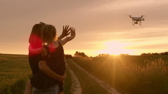 ws 어머니와 딸 일몰에서 비행 하는 무인을 흔들며 - 무인항공기 스톡 비디오 및 b-롤 화면
