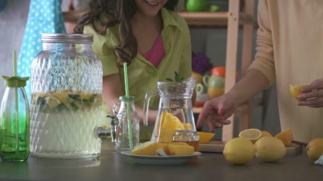 vídeos de stock e filmes b-roll de mother and daughter working as a team while making a lemonade - limonada tradicional