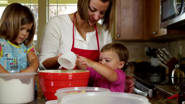 Mother and daughters in kitchen baking cookies together video
