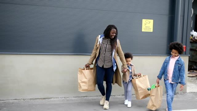 vídeos y material grabado en eventos de stock de madre e hijas caminando hacia el coche llevando bolsas de compras en un desván de estacionamiento - madre e hijos