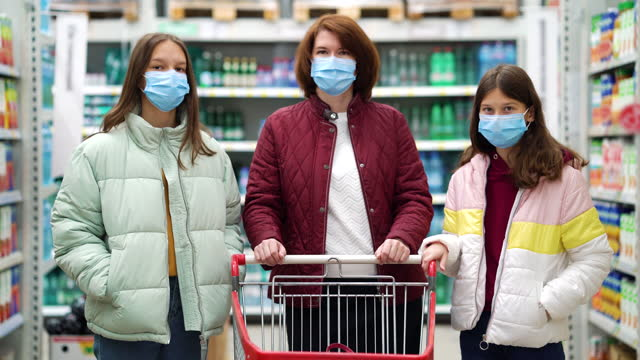 Mother and daughters with shopping cart in supermarket during pandemic video