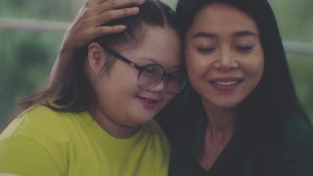 vídeos y material grabado en eventos de stock de madre y síndrome de down hija abrazando - posición descriptiva