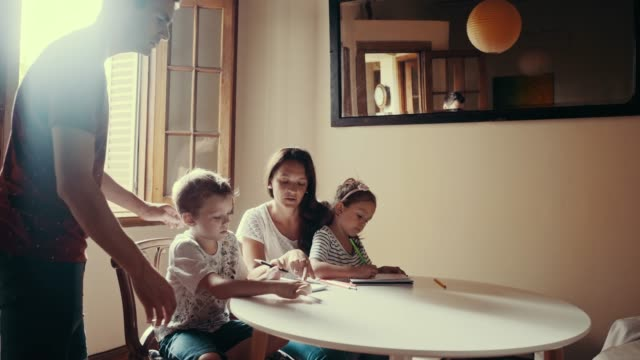 Mother and father are spending time with children drawing (slow motion)