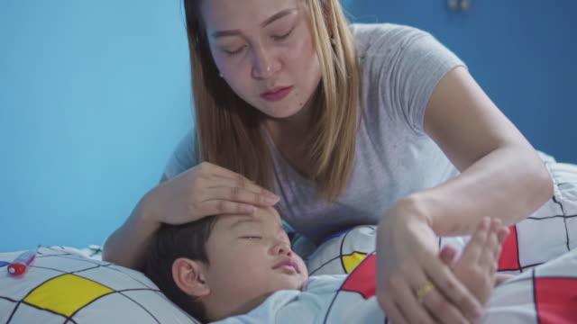 madre e padre che si prendono cura del figlio malato,slow motion - china drug video stock e b–roll