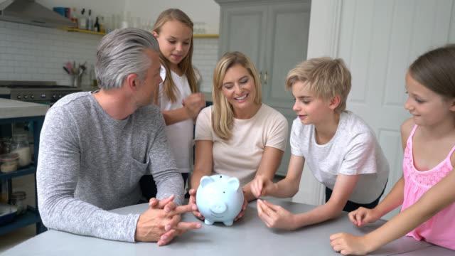 Mother and father teaching their children to save money video