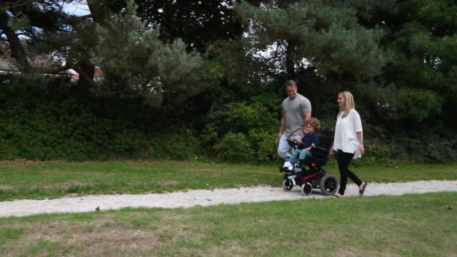 vídeos de stock, filmes e b-roll de mãe e pai caminhando com o filho na cadeira de rodas - acessibilidade