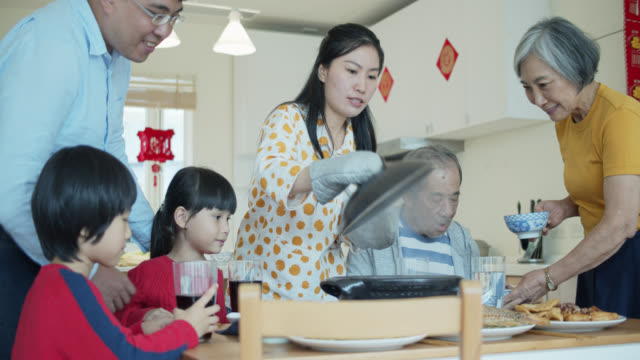 春節期間母親和祖母帶著食物餐桌吃家庭餐 - chinese new year 個影片檔及 b 捲影像