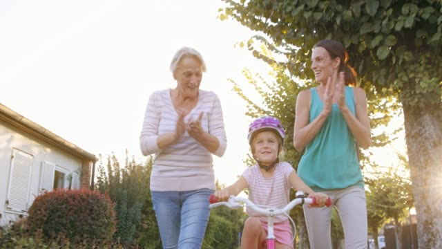 SLO MO Mother and grandmother teaching the little girl ride the bike and cheering for her Slow motion wide low angle dolly shot of a little girl learning to ride the bike with the help of her mother and grandmother running next to her and cheering for her. Shot in Slovenia. tank top stock videos & royalty-free footage