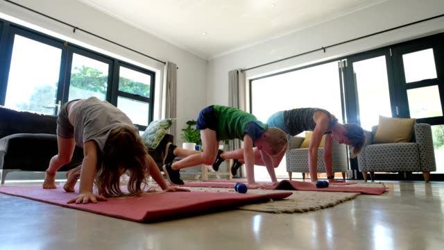 vídeos de stock e filmes b-roll de mother and her children doing an online fitness class at home - isolado
