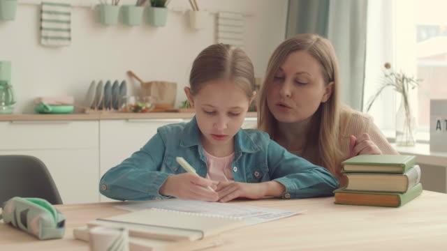 мать и ее дочь делают домашнее задание вместе - covid testing стоковые видео и кадры b-roll