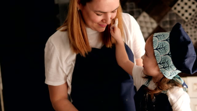anne ve kızı eğlenir ve kızı annenin yüzünü unla lekeler. - çocuk bayramı stok videoları ve detay görüntü çekimi