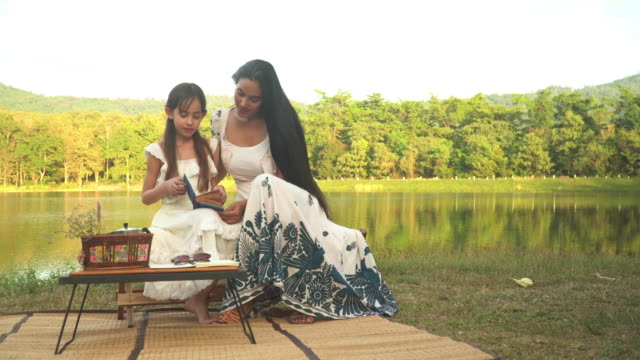 mother and her daughter spend weekend time having picnic and reading book together