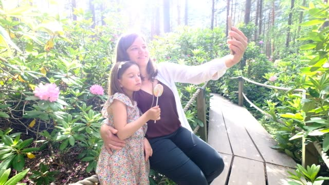Mother and her daughter take a selfie in Rhododendrons Park. It is one of the most popular and beautiful places in Helsinki, Finland.