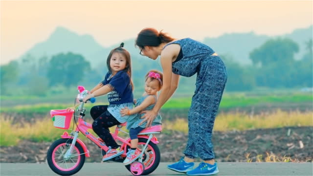 Mother and her daughter with bicycle in countryside together video