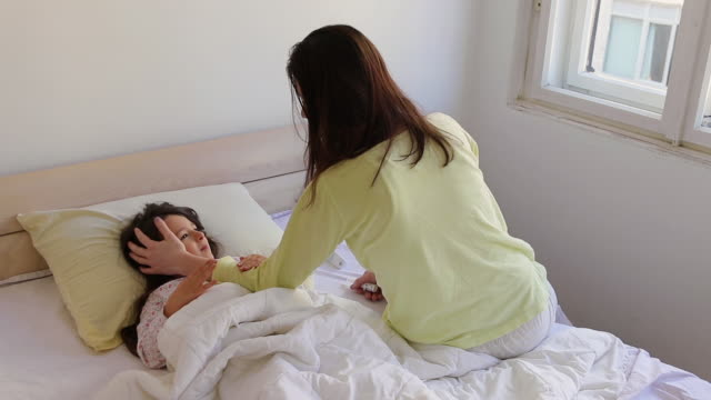 Mother and her ill daughter in bedroom Mother expressing love to her ill daughter in bedroom double bed stock videos & royalty-free footage