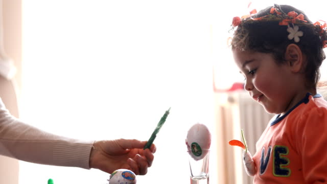 Mother and her little daughter painting Easter eggs video