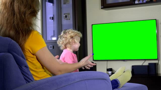 vídeos de stock e filmes b-roll de mother and her naughty daughter girl watching tv. green chroma key screen - tv e familia e ecrã