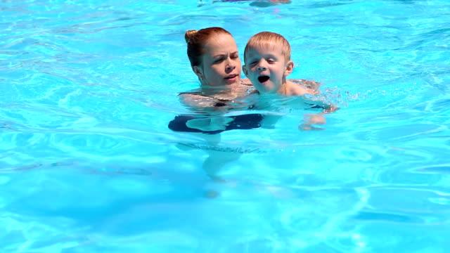 mor och hennes son som har kul i en pool. - enbarnsfamilj bildbanksvideor och videomaterial från bakom kulisserna