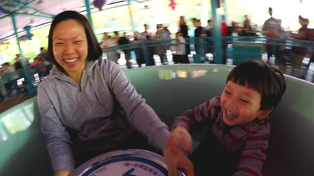 mutter und sohn sitzen auf einer rotierenden stuhl tasse genießen die geschwindigkeit der stimulation und umklammert das lenkrad im vergnügungspark auf den urlaub ferien. - volksfest stock-videos und b-roll-filmmaterial