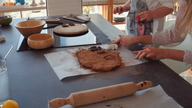 Mother and her toddler bonding while making cookies Video of cute three year old girl assisting her mother in cutting out shapes in a dough with cookie cutters while they are preparing tasty vegan dessert together. cookie cutter stock videos & royalty-free footage