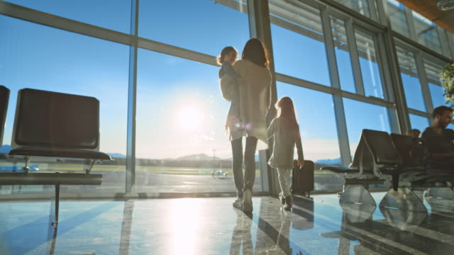 mother and her two children looking out the glass wall of the airport building and onto the runway in sunshine - аэровокзал стоковые видео и кадры b-roll