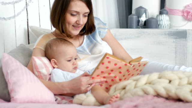 mother and her two years old baby boy are reading book in sunny room - comparsa video stock e b–roll