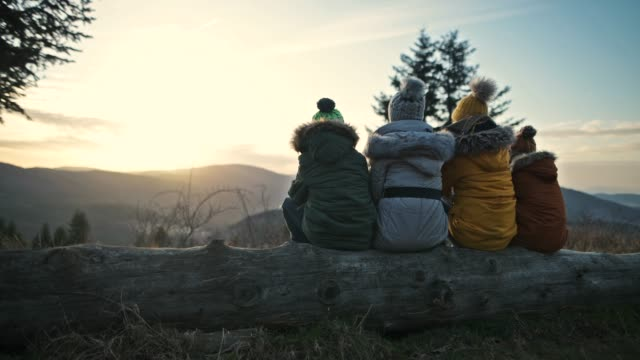 mother and kids enjoying sunset in mountains - abiti pesanti video stock e b–roll
