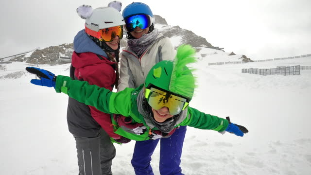 Mother and kids having fun skiing in Alps