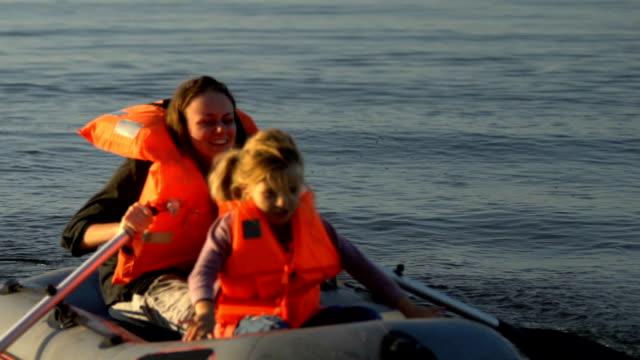 мать и маленькая дочь выходят на берег на спасательной шлюпке, спасаясь после кораблекрушения - кораблекрушение стоковые видео и кадры b-roll
