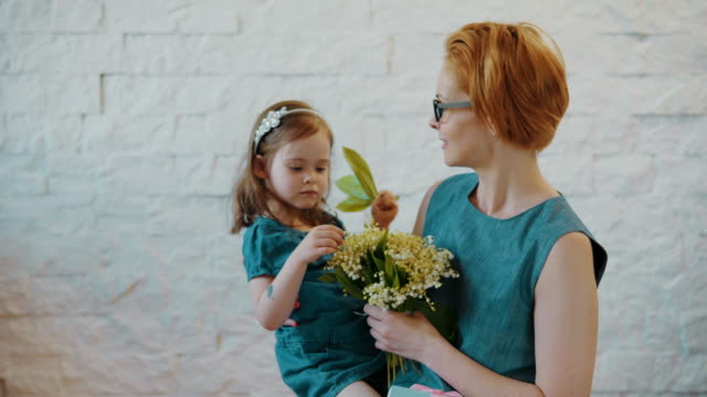 Mother and little daughter hug each other with flowers video