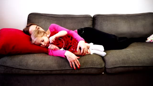 en mor och lilla dotter ligga på soffan och somna. - cosy pillows mother child bildbanksvideor och videomaterial från bakom kulisserna
