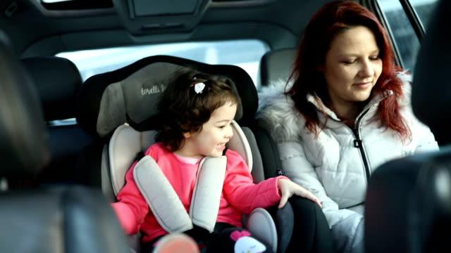 vídeos de stock e filmes b-roll de mother and little daughter on back seat in car - proteção