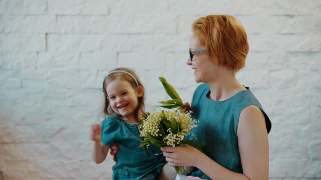 Mother and little daughter smell beautiful flowers video