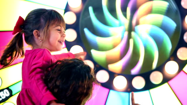 Mother and little girl in arcade video