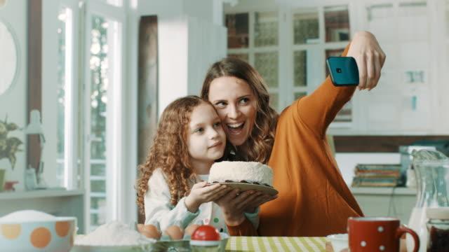 mor och liten flicka tar selfie med födelsedagstårta - birthday celebration looking at phone children bildbanksvideor och videomaterial från bakom kulisserna
