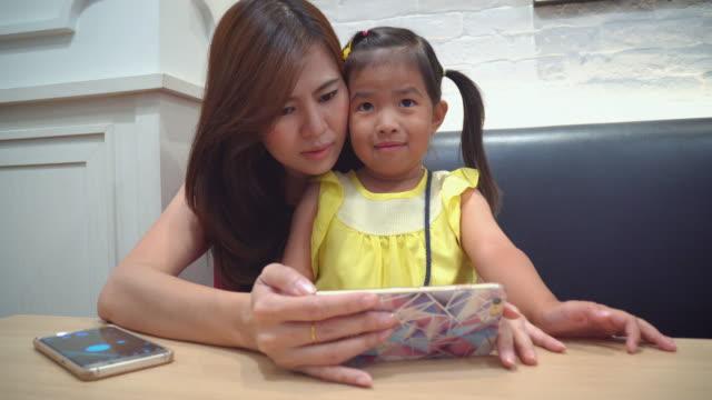mor och liten flicka med smartphone i caféet - birthday celebration looking at phone children bildbanksvideor och videomaterial från bakom kulisserna