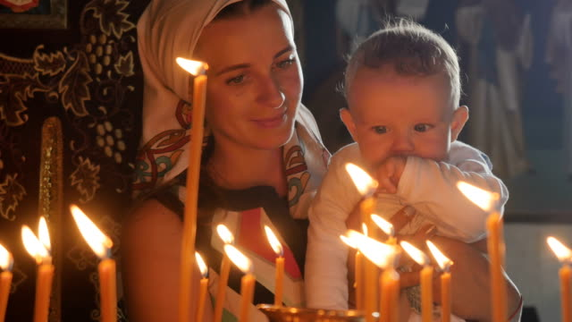 Mother and little son observes the burning candles in the church video