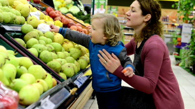 Mother and son at grocery store Mother and son at grocery store. pear stock videos & royalty-free footage