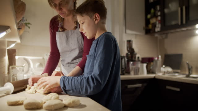 Mother and son baking bread buns