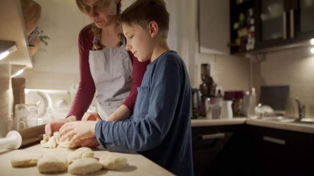 vídeos de stock e filmes b-roll de mother and son baking bread buns - baking bread at home