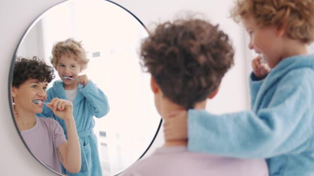 一緒に微笑む鏡を見て、バスルームで歯を磨く母と息子 - ブラシ点の映像素材/bロール