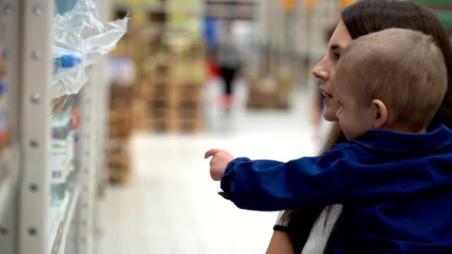 母と息子は店やスーパーで水を買う ビデオ