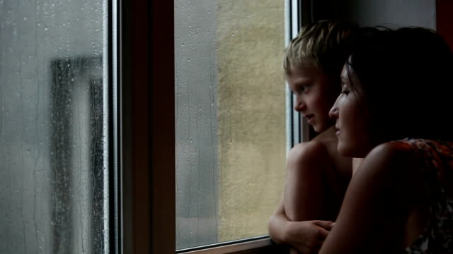 Mother and son conversation on the windowsill during autumn rainy day video